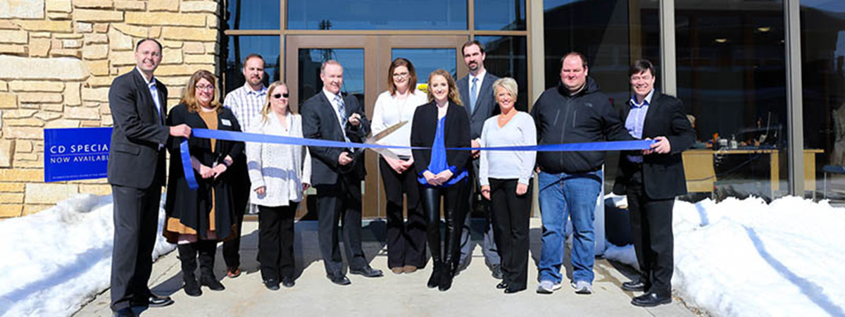 bank employees cut a blue ribbon in front of renovated