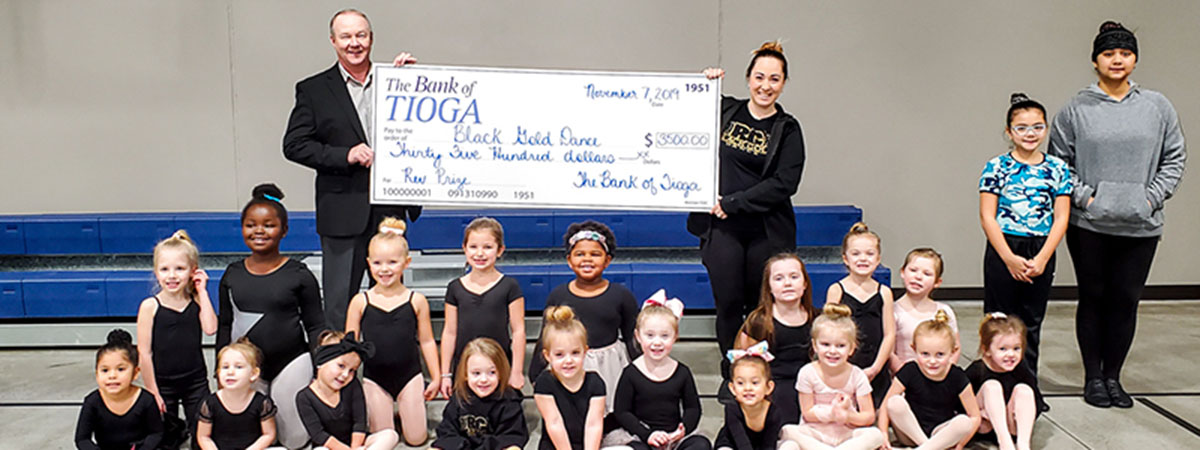 employee and dancers pose with large check